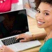 Mulher na mesa do escritório digitando no notebook