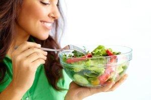 Mulher segurando um bowl de saladas