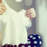 Uma mulher escolhendo roupas para seu bebê